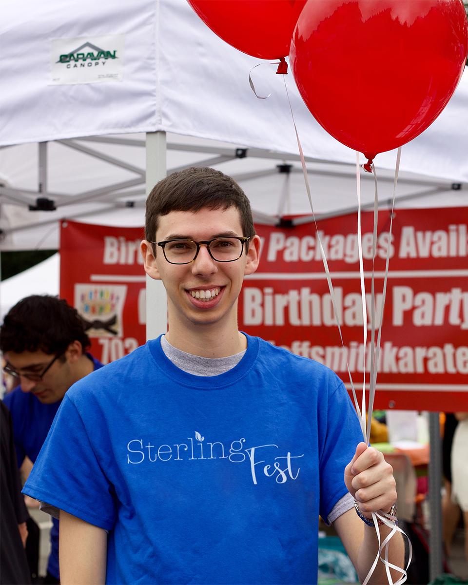 A smiling young man holding a bundle of red balloons at SterlingFest 2018