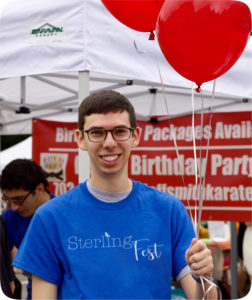 A young man holding red balloons at SterlingFest