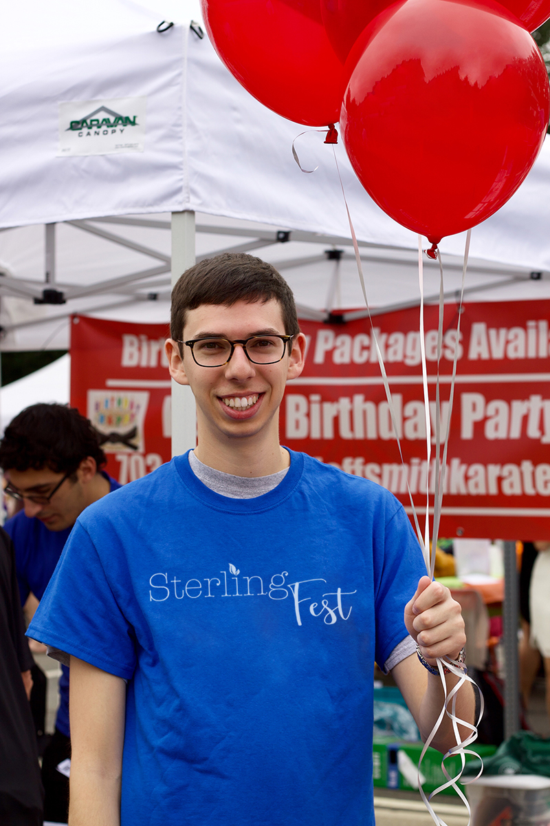 A young man wearing a SterlingFest tshirt holding a bundle of red balloons