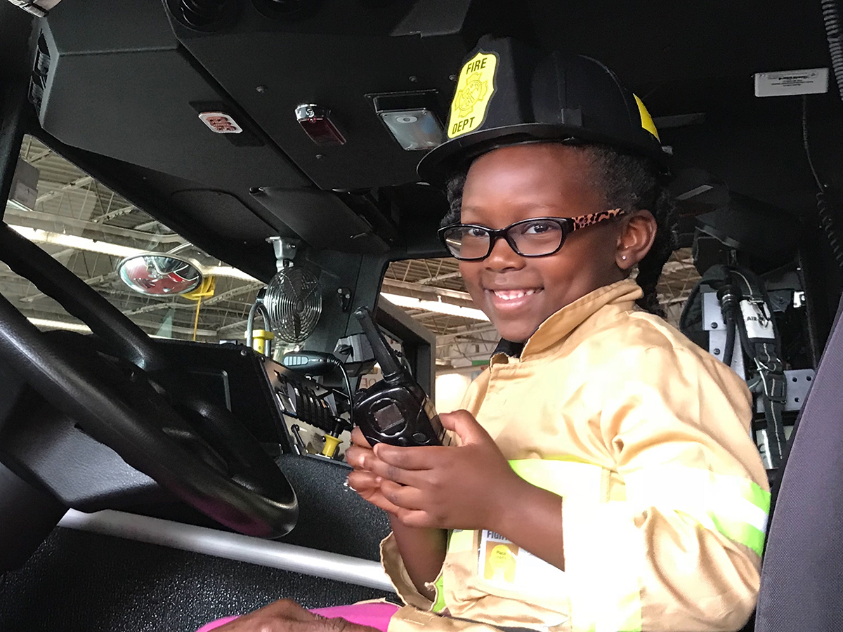 A little girl enjoys sitting inside a fire truck at the Sterling Fire Department's Open House next to SterlingFest