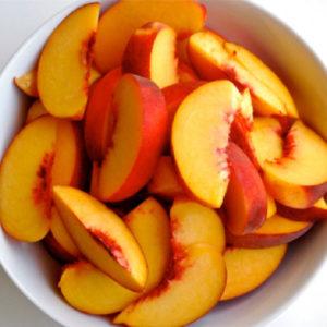 Fresh sliced peaches in a white bowl